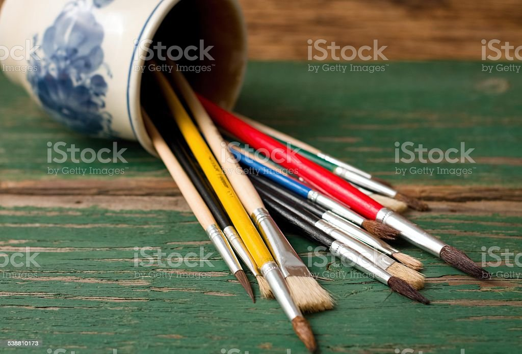 Spilled ceramic cup with paintbrushes on green board stock photo