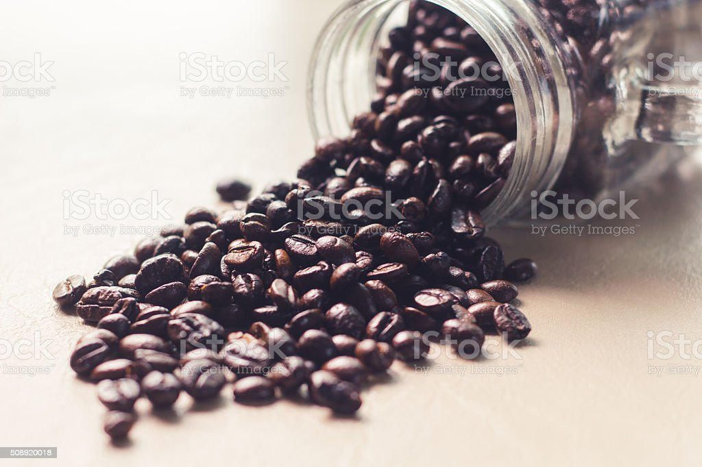 Spilled coffee beans from the Mason jar. stock photo