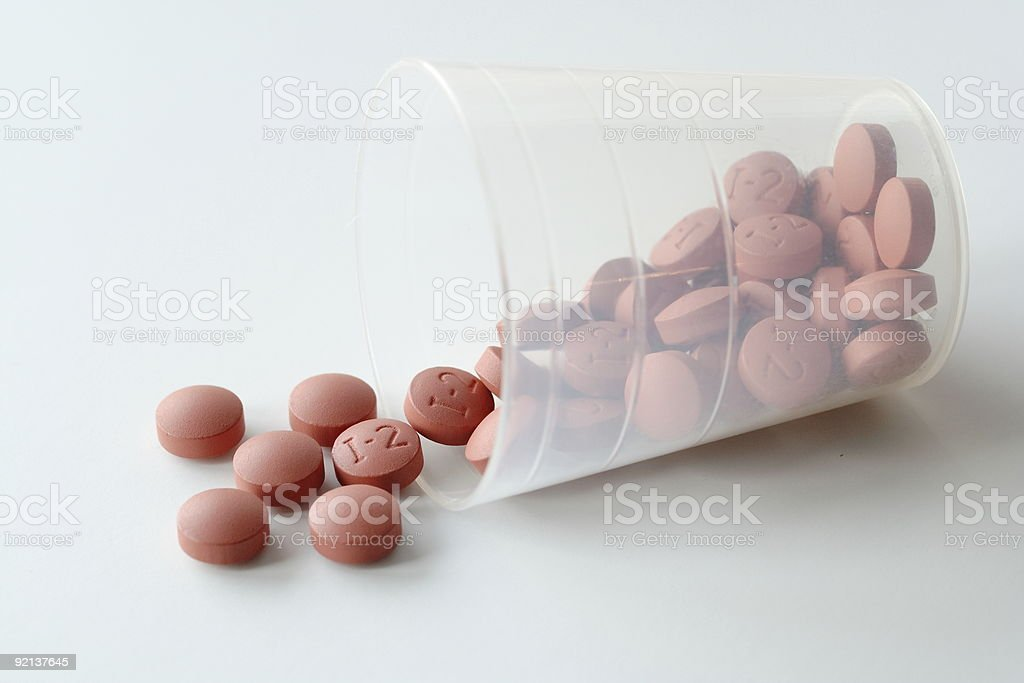 Spilled cup of brown pain pills stock photo