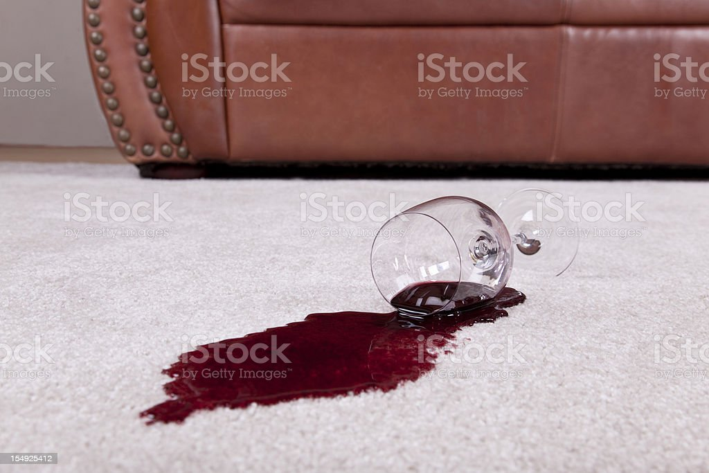 Spilled glass of wine on new carpet stock photo