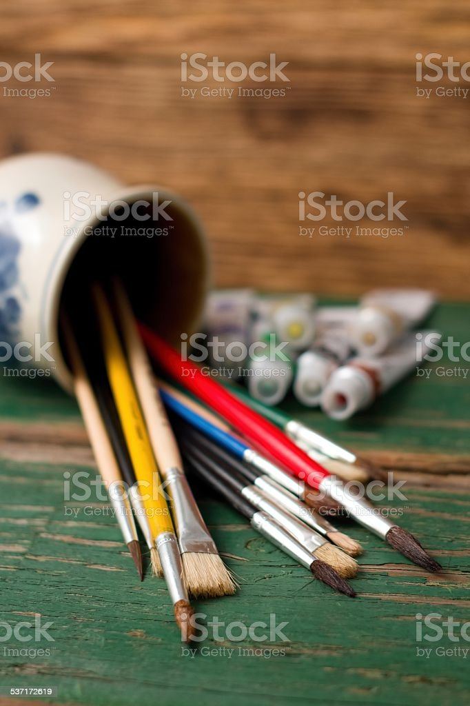 Spilled jar with different paintbrushes and acrylic colors stock photo