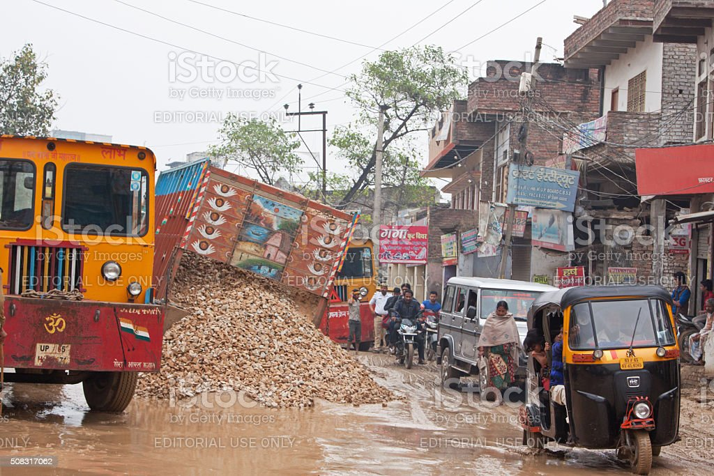 Spilled load from a truck on a collapsed road, India stock photo