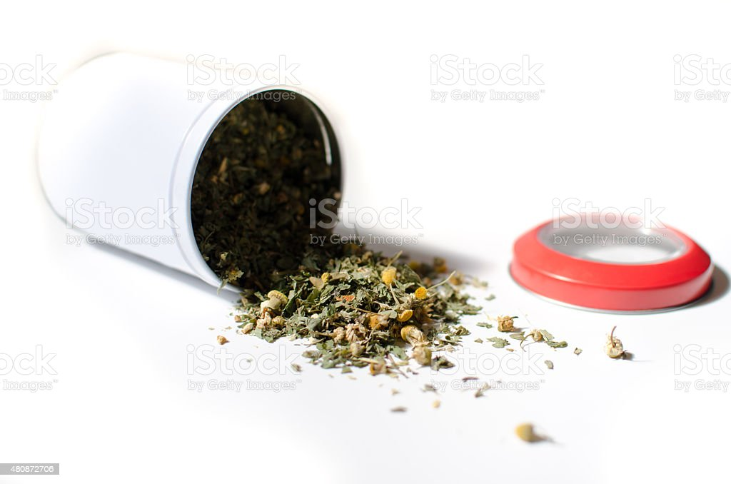 Spilled loose bio tea pot with a red lid stock photo