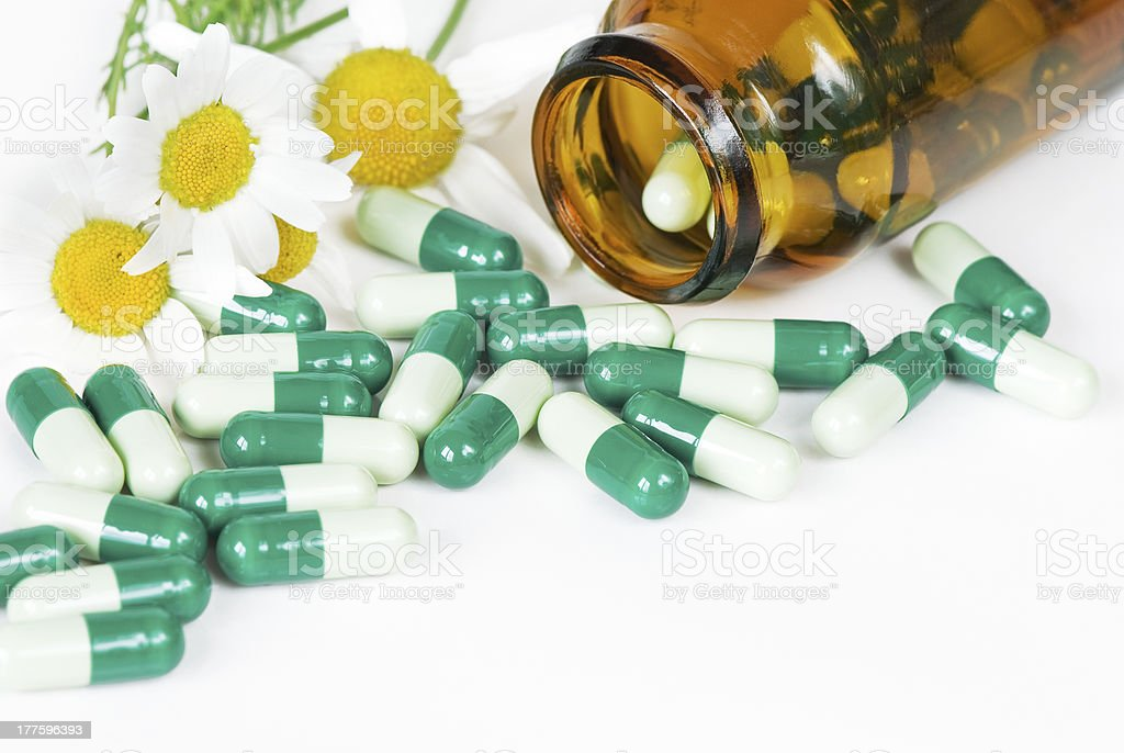 spilled pills, a bottle and two flowers of chamomile royalty-free stock photo