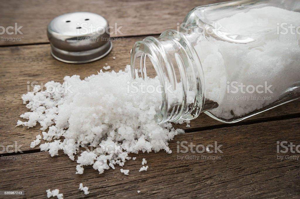 Spilled salt with salt shaker on wooden background stock photo