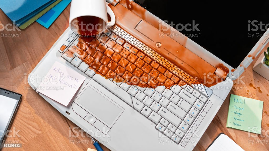 Spilling coffee on laptop stock photo