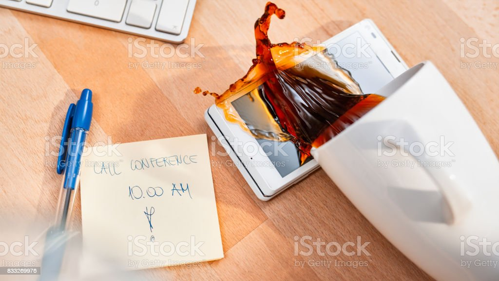 Spilling coffee on smart phone stock photo