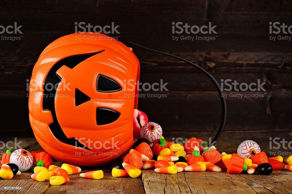 Spilling Halloween Jack o Lantern candy pail on wood stock photo