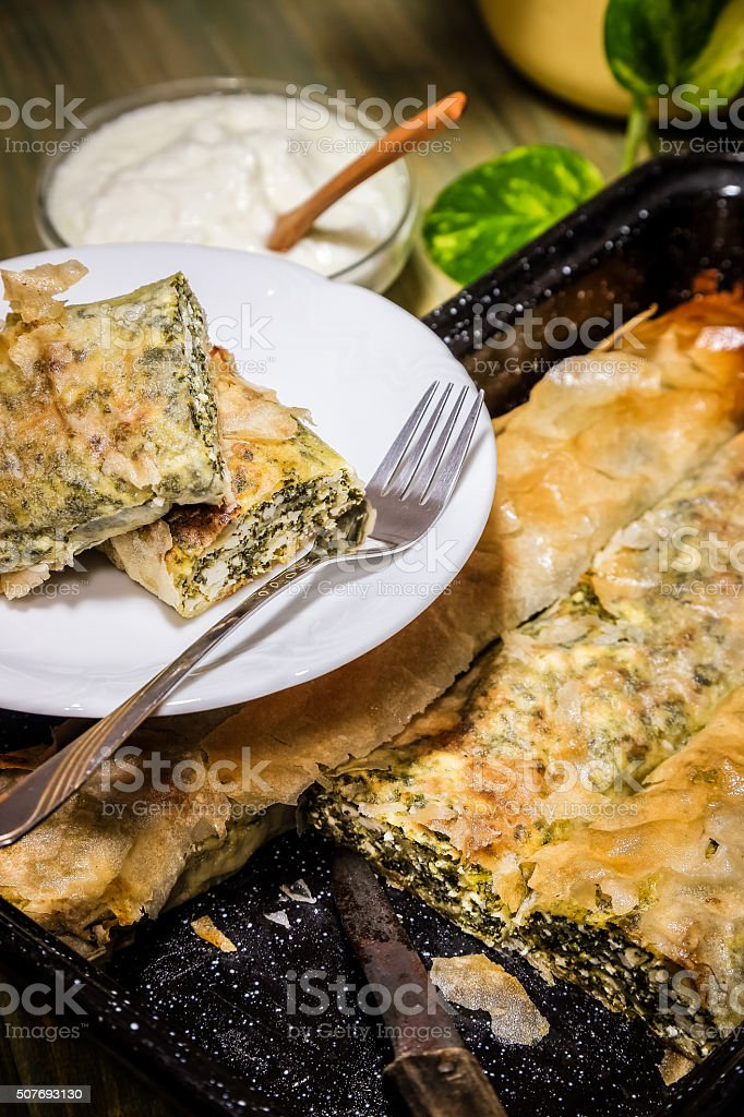 Spinach and feta pie in filo pastry, with Greek yogurt stock photo