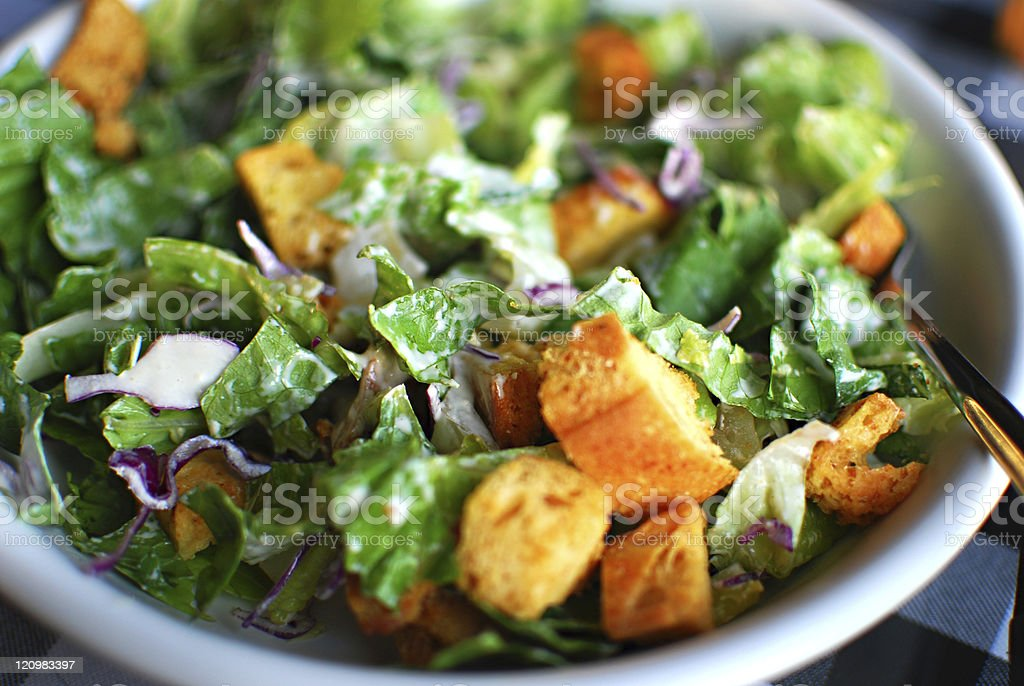 Spinach and lettuce salad with croutons in a white bowl stock photo