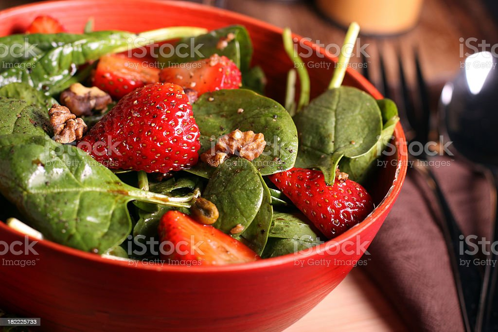 Spinach and strawberry salad in red bowl stock photo