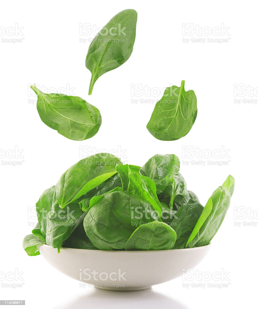 Spinach leaves fall into white bowl stock photo