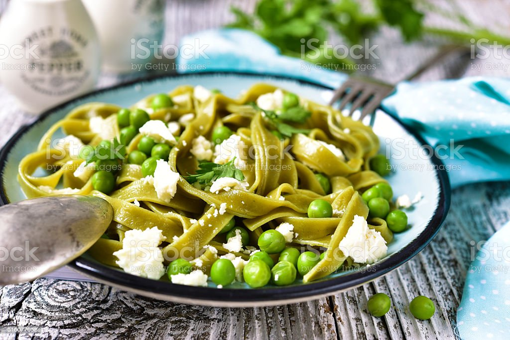 Spinach pasta with green pea and cheese. stock photo