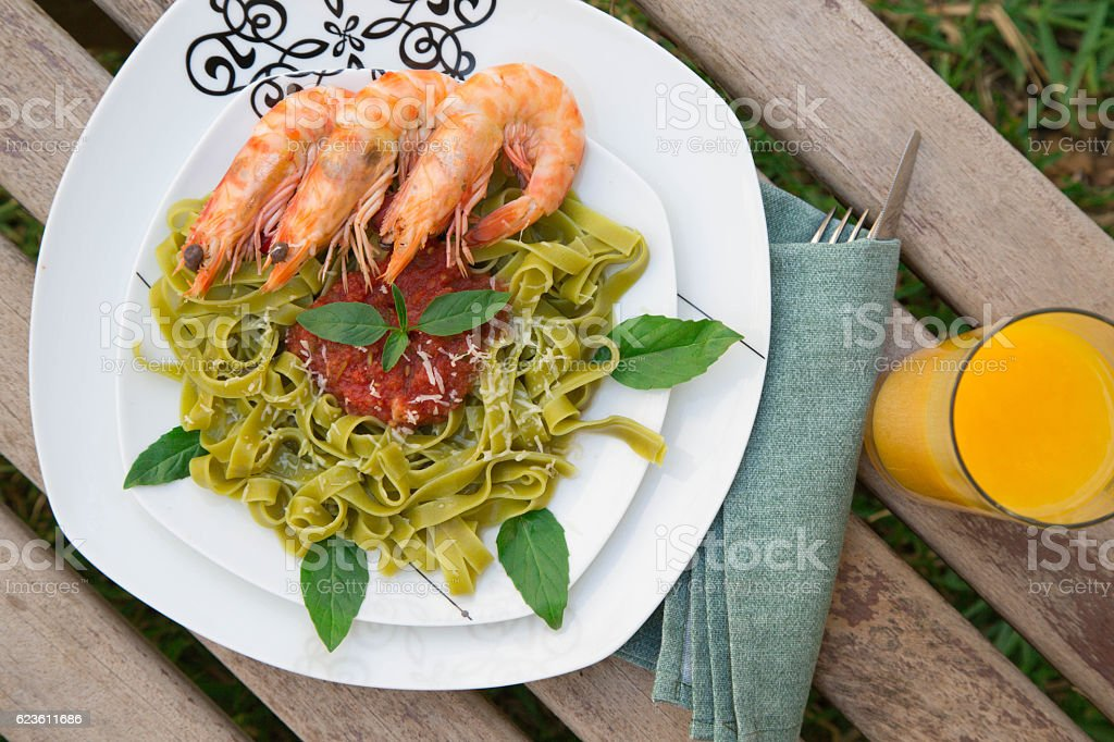 Spinach pasta with shrimps and tomato sauce. stock photo