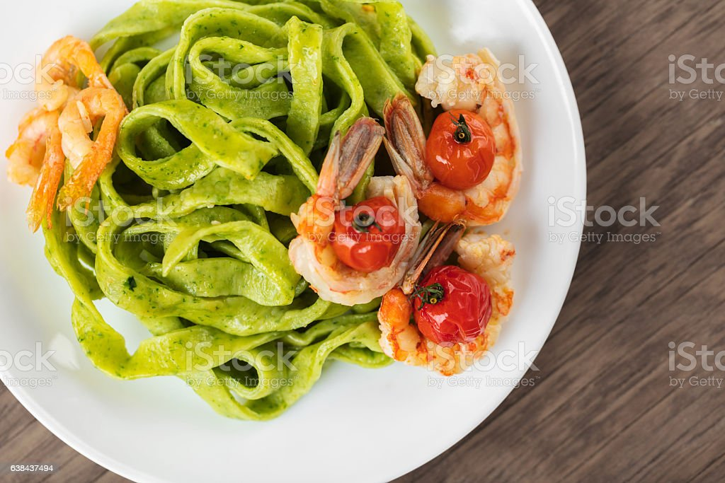 Spinach pasta with shrimps stock photo