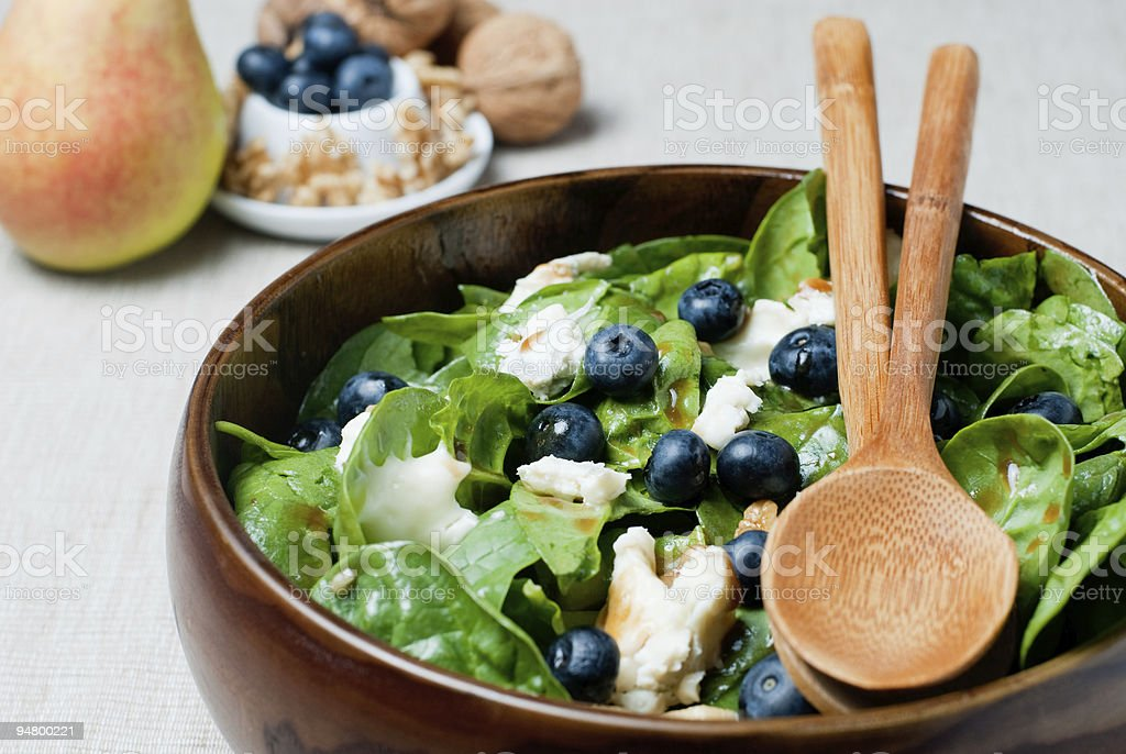 Spinach salad with berries and chicken in a wooden bowl royalty-free stock photo