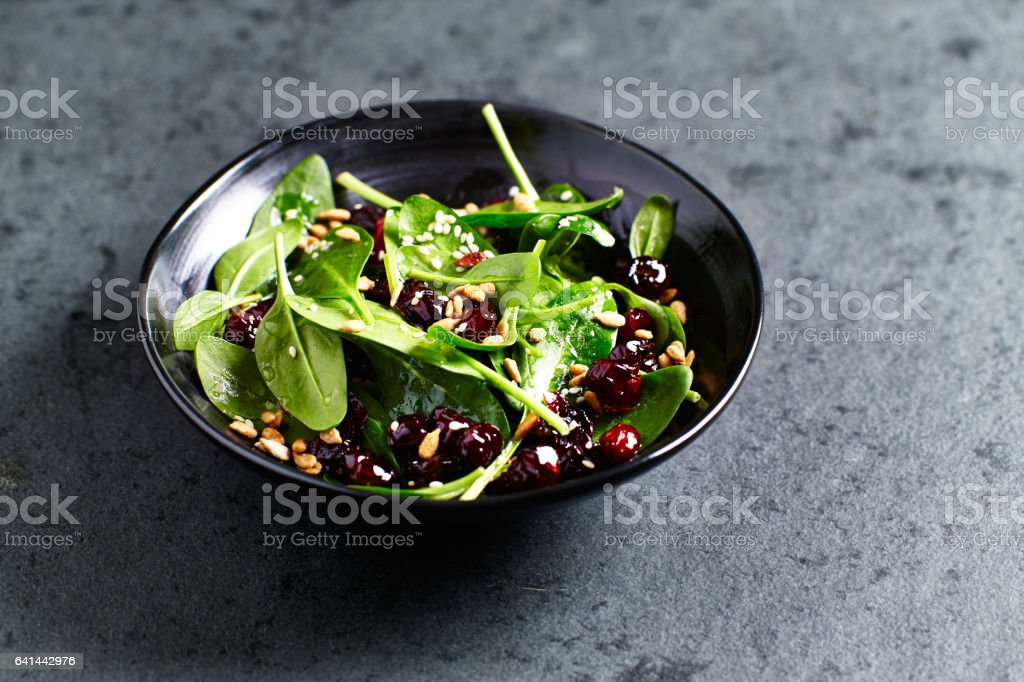 Spinach salad with dried cranberries and pomegranate seeds stock photo