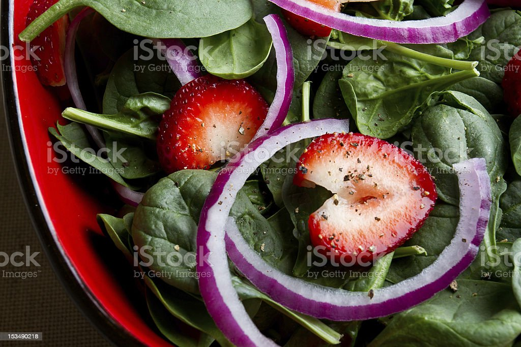 A spinach salad with sliced strawberries and red onions stock photo