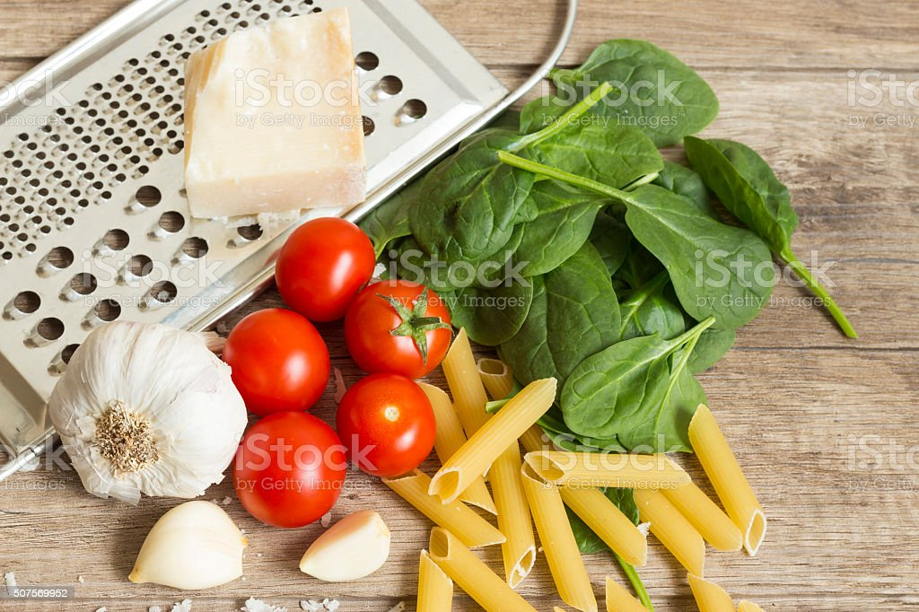 Spinach with garlic, cherry tomatoes, parmesan cheese and pasta stock photo
