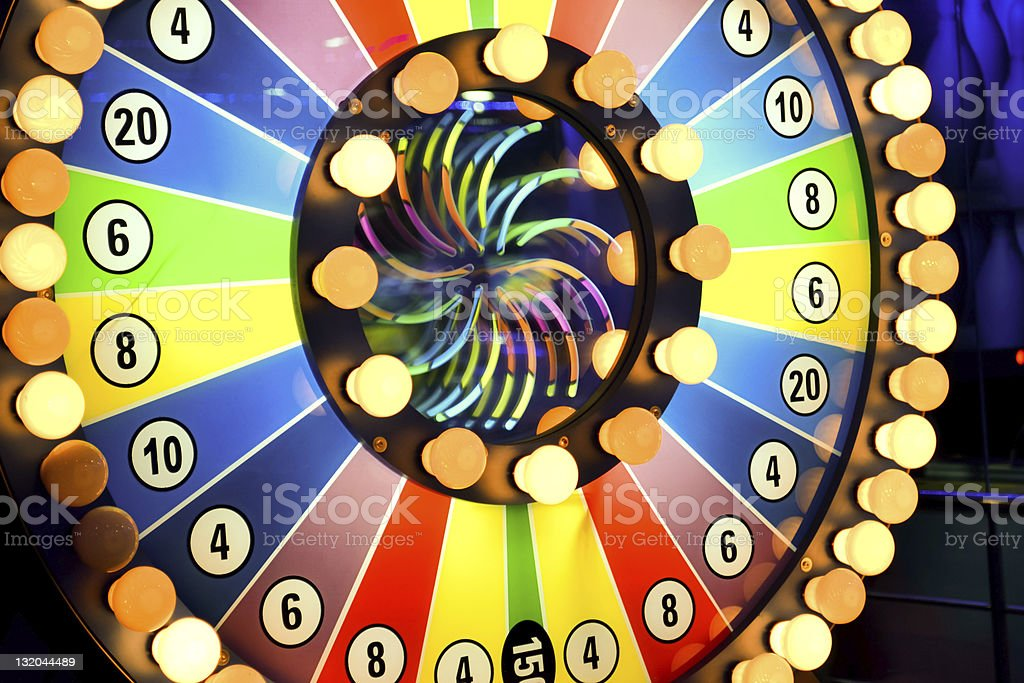 Spinning wheel of fortune with light bulbs and colors  stock photo