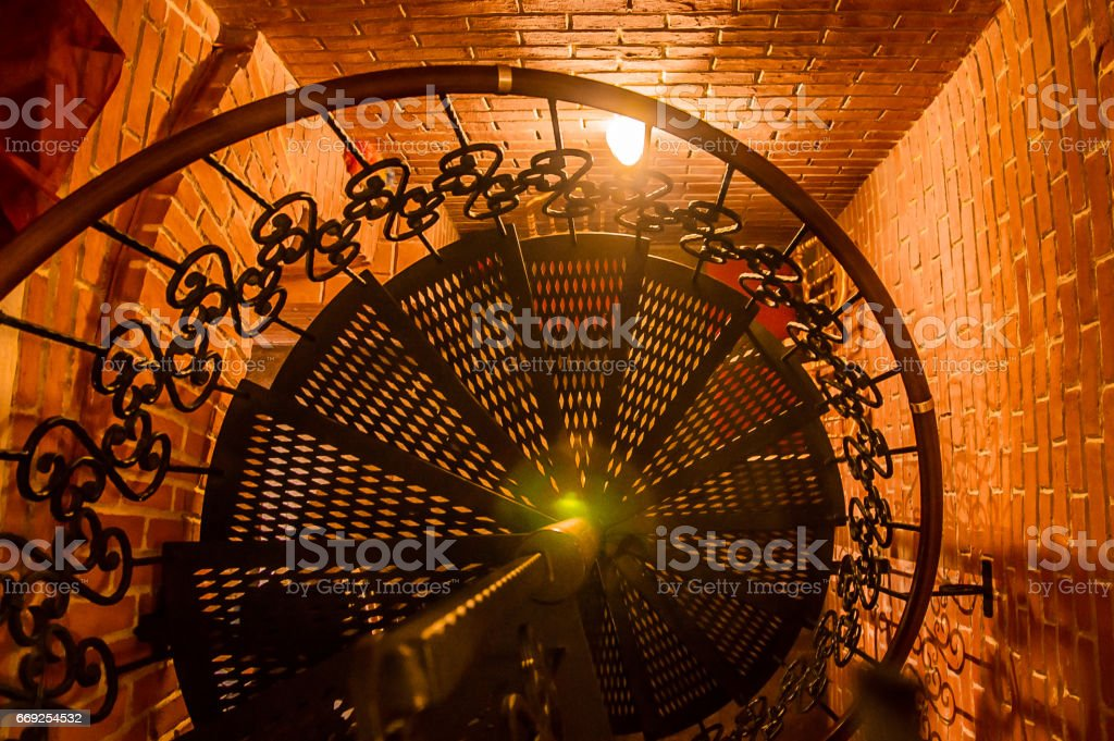 spiral iron stairs in the brick staircase stock photo