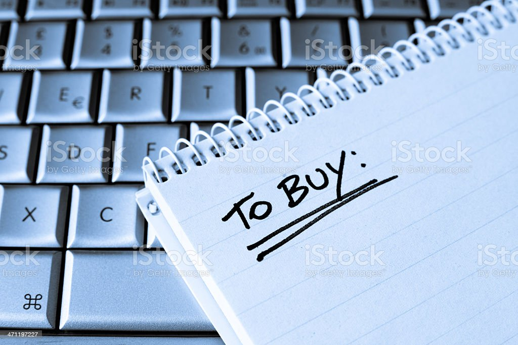 Spiral notebook on Laptop with blank To Buy List stock photo