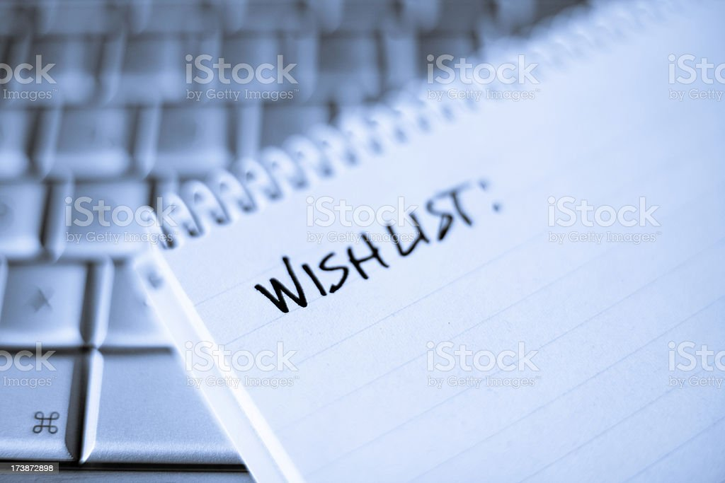 Spiral notebook on Laptop with blank Wishlist stock photo