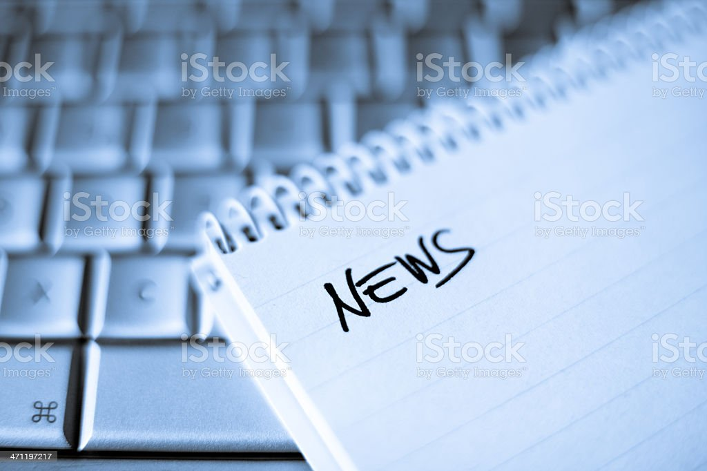 Spiral notebook on Laptop with News writing stock photo