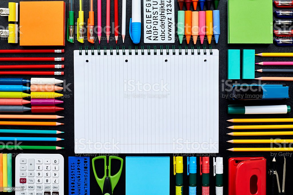 Spiral notebook surrounded by school supplies on blackboard stock photo