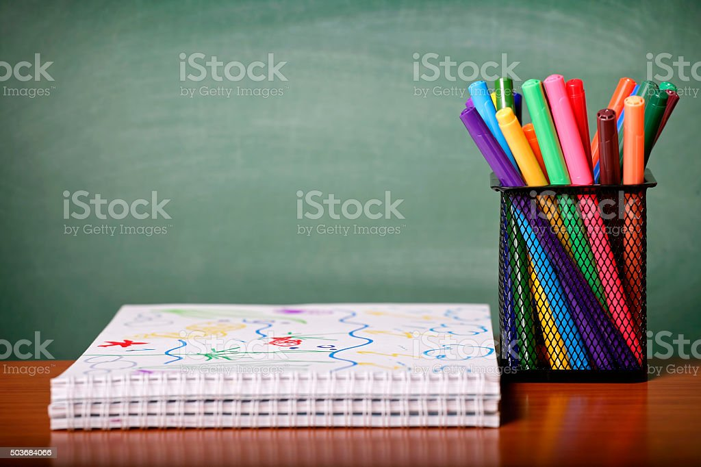 Spiral notebooks and felt tip pens on chalkboard background. stock photo