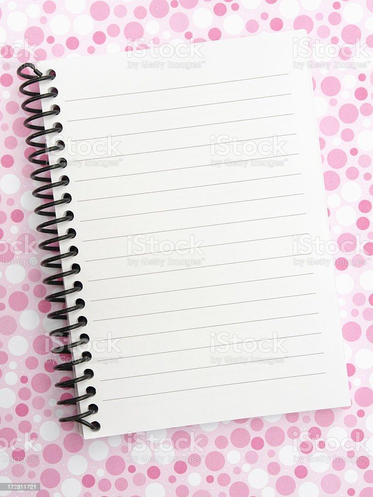 Spiral notepad on pink polkadot surface royalty-free stock photo