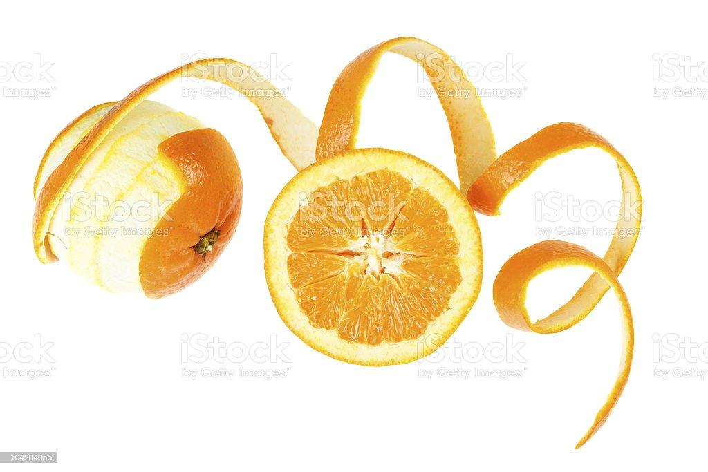 Spiraling oranges peel next to halved orange royalty-free stock photo