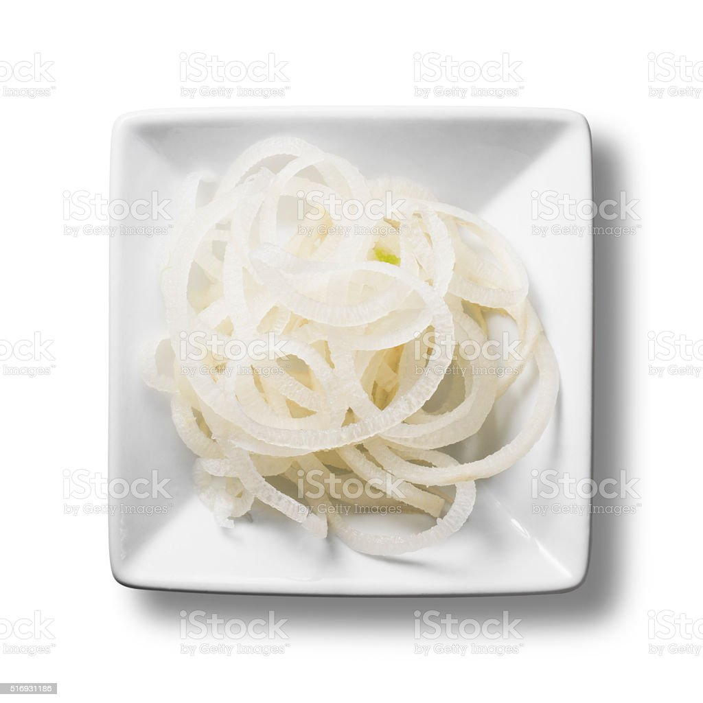 Spirals of fresh white radish isolated in a white bowl stock photo