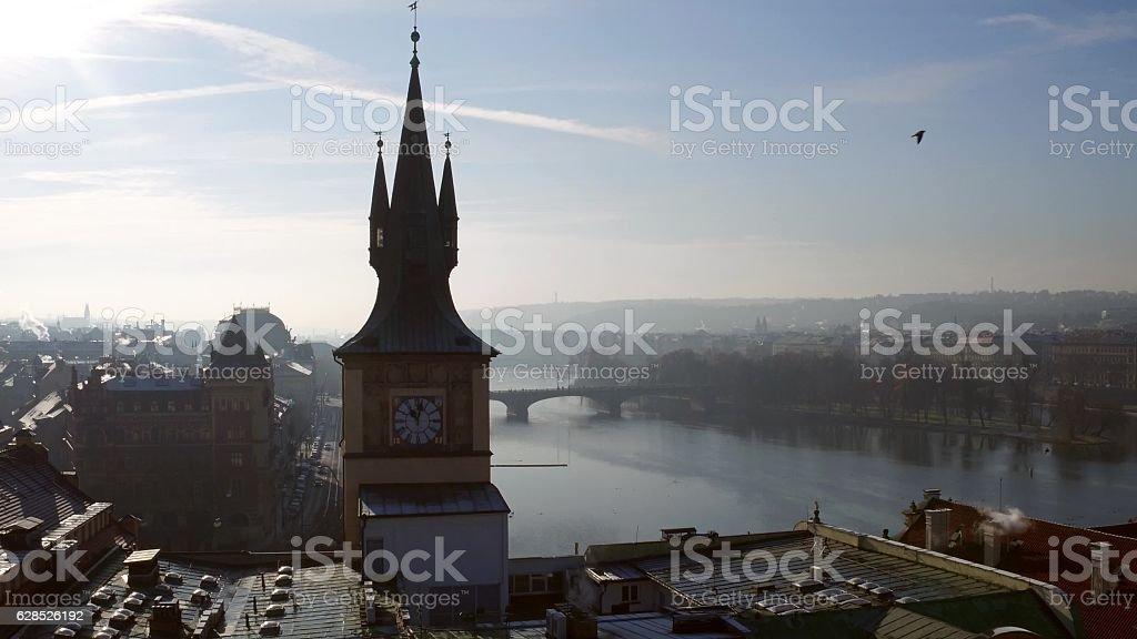 Spired clock tower against Vltava river in Prague on a stock photo