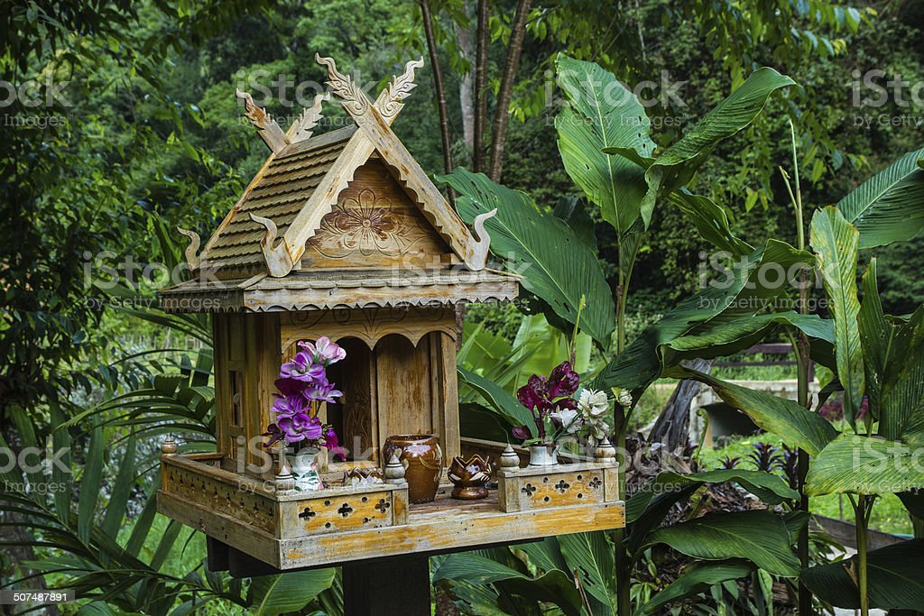 spirit house in thailand with flowers in vases and some wreathes stock photo