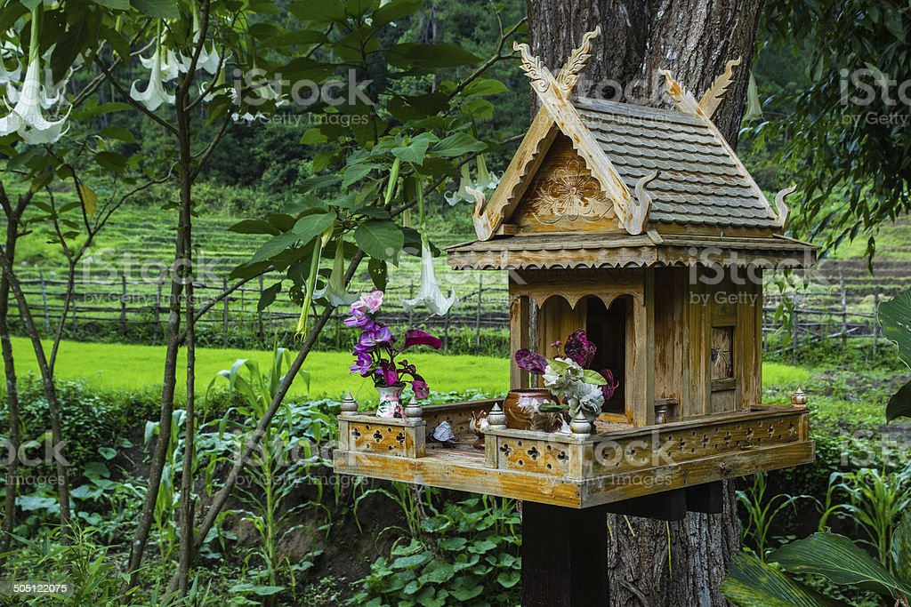 spirit house in thailand with flowers in vases stock photo