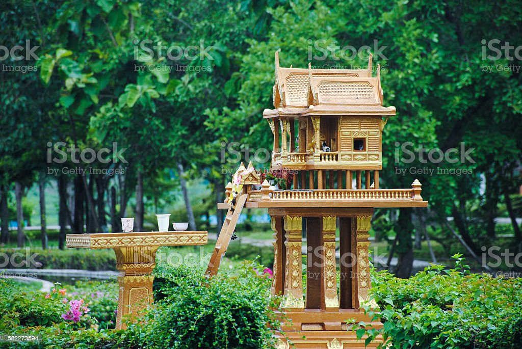 spirit house in thailand with garland and some wreathes, joss house stock photo