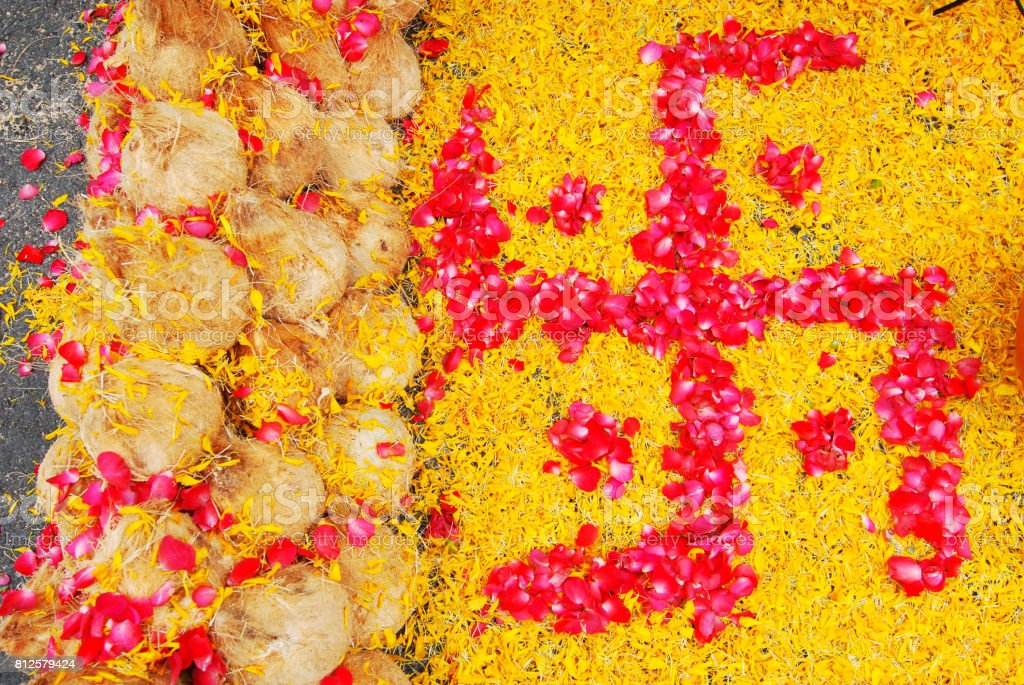 Spiritual Hindu, Buddhist and Jain Symbol - Swastika icon decorate with yellow and red flower and It is a sign of nourishment. stock photo