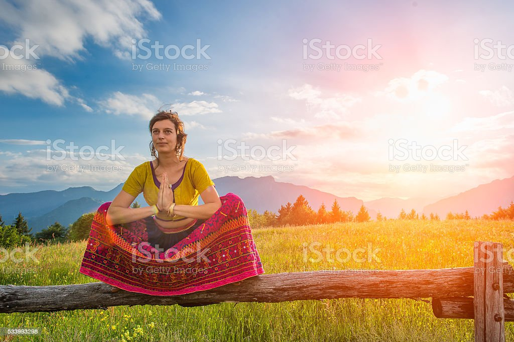 Spiritual practices of a girl sitting on fence stock photo