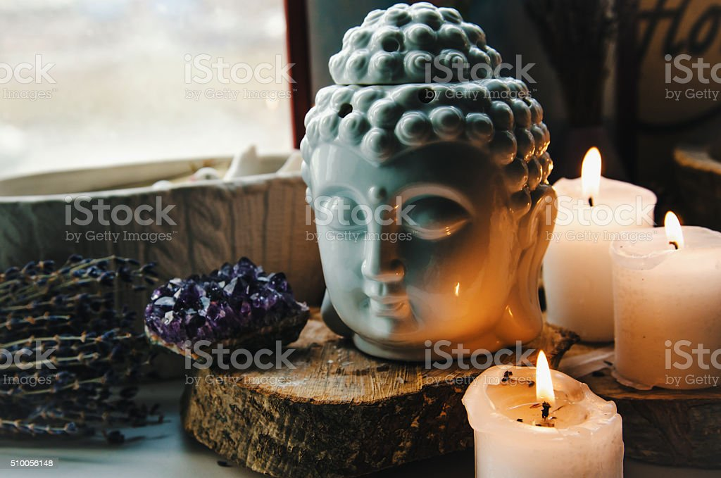 spiritual ritual meditation face of Buddha ametist candles on old stock photo