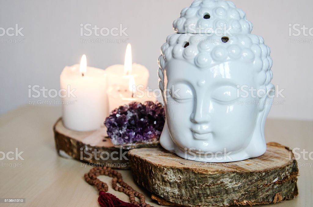 spiritual ritual meditation face of Buddha ametist candles on wooden stock photo