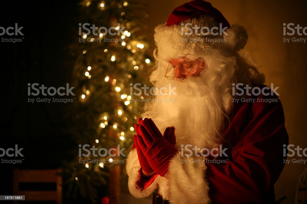 Spiritual Santa Praying at Home with Christmas Tree in Background stock photo