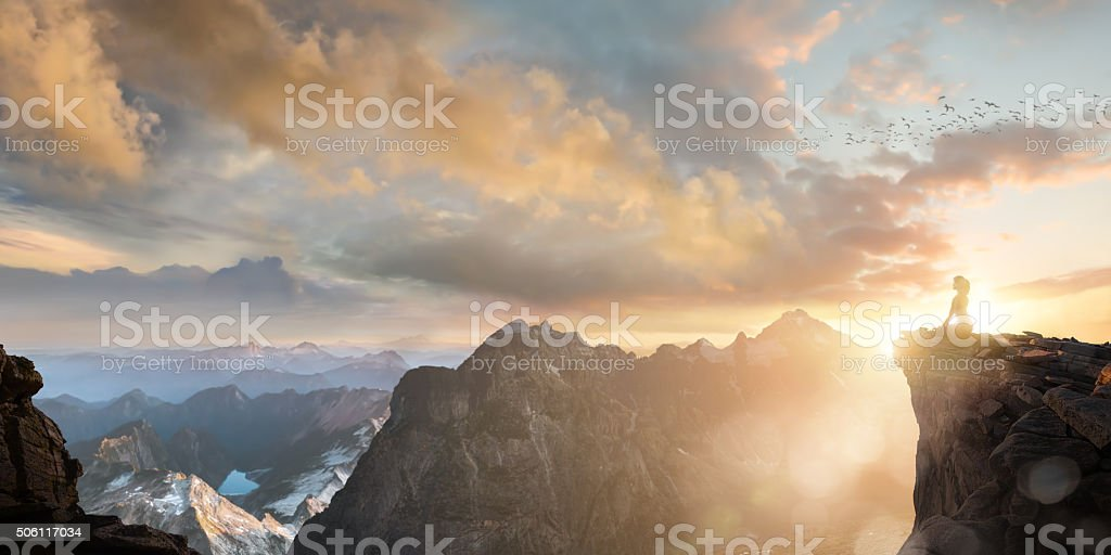 Spiritual Seeker Meditating High On Mountain Top At Sunset stock photo