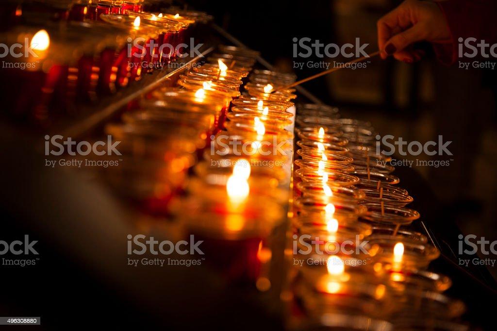 Spirituality.  Lighting red candles in Catholic church. stock photo