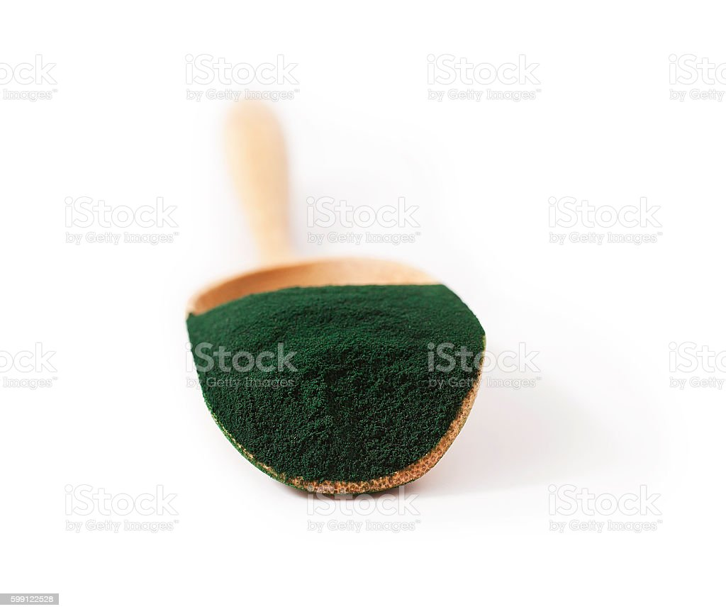 Spirulina algae powder in the wooden scoop stock photo