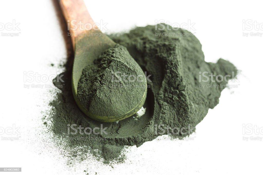 Spirulina algae powder on wooden spoon stock photo