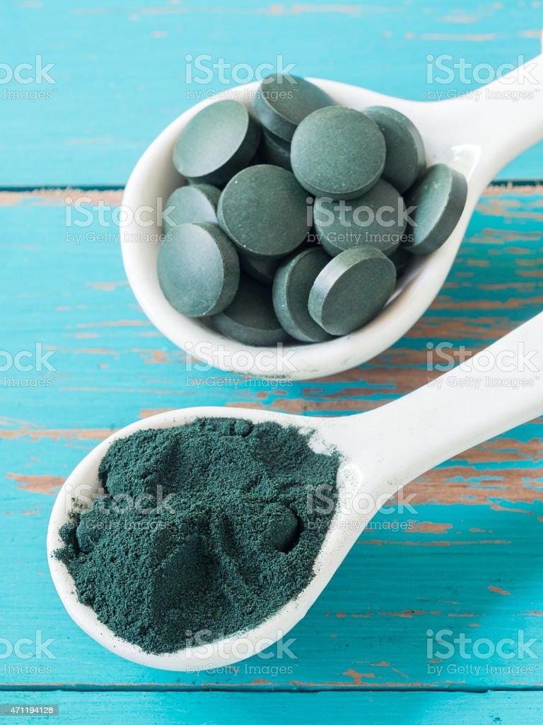 Spirulina powder and tablets stock photo