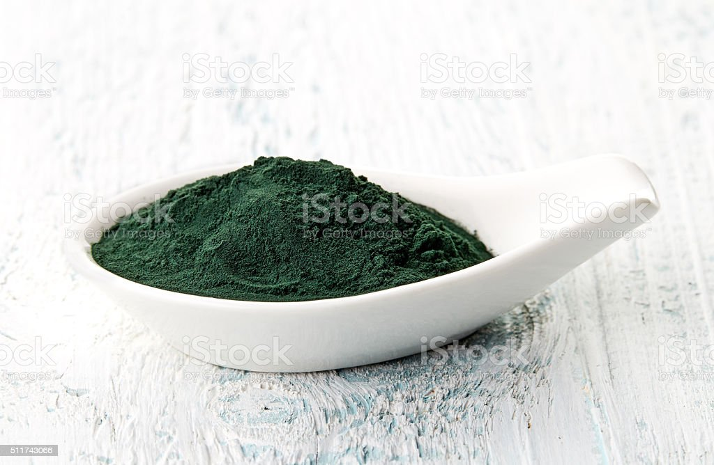 Spirulina powder in white porcelain spoon stock photo