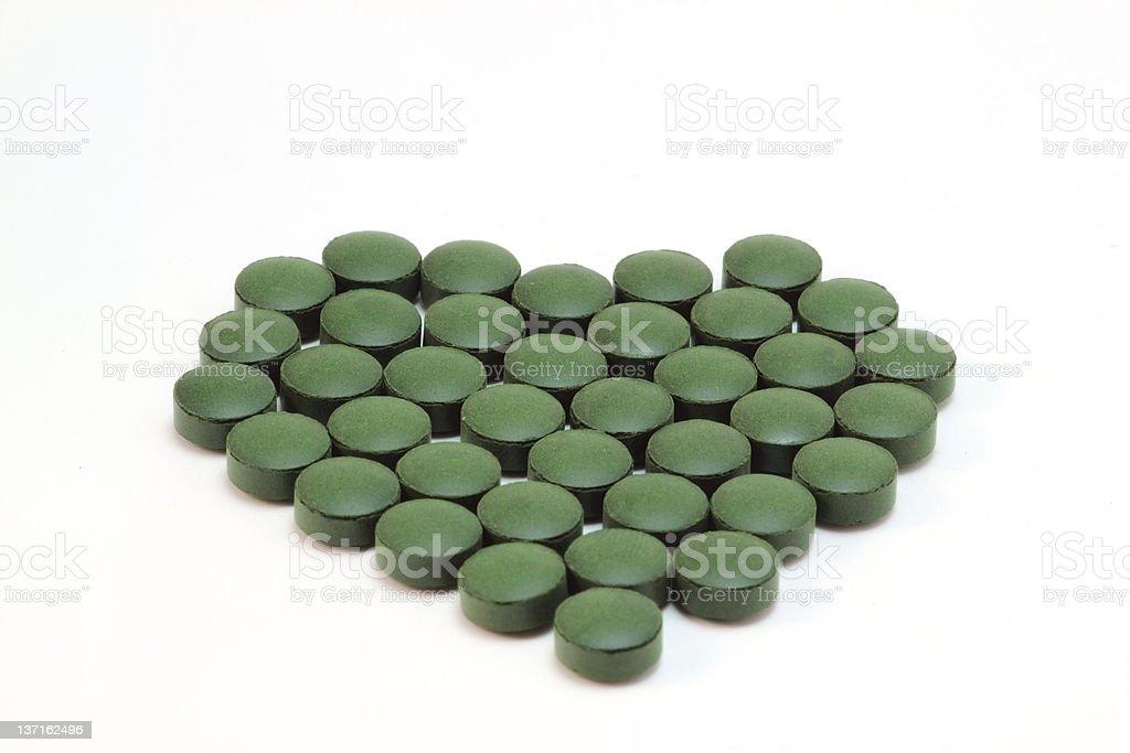 Spirulina tablets in heart shape stock photo