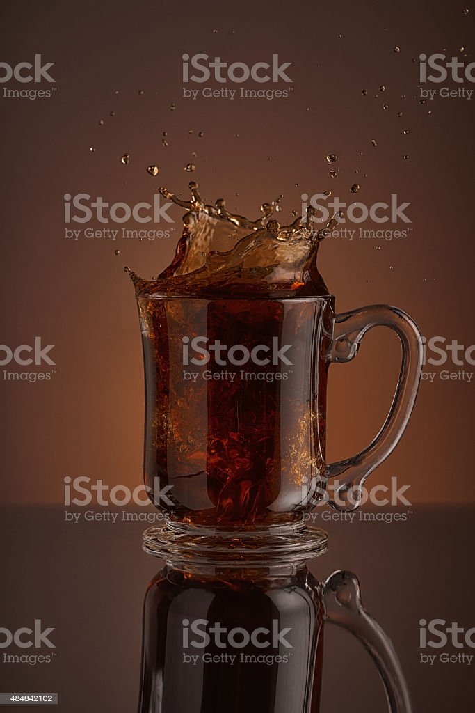 Splash of  black coffee drink on a brown background. stock photo